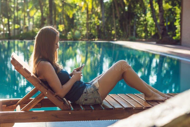 Entspannender naher Swimmingpool der glücklichen Smartphonefrau Schönes Mädchen, das ihre Daten Handy App 4g verwendet, um Lieder stockfotos