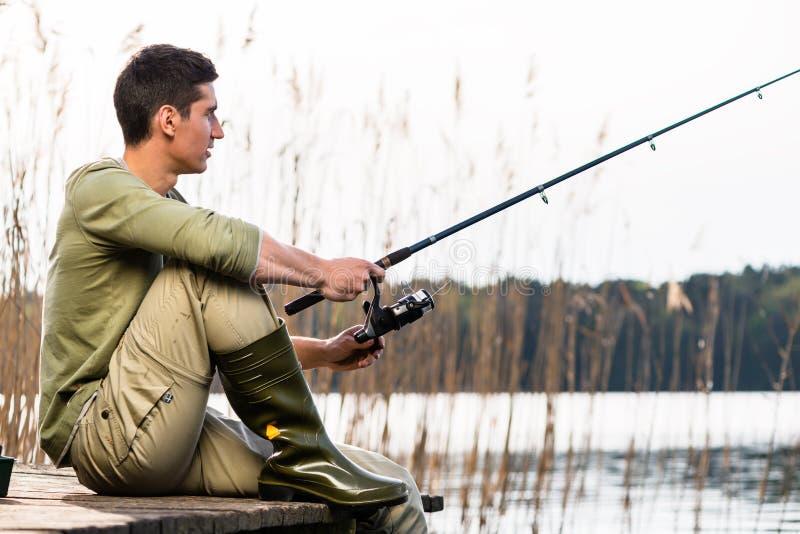 Entspannendes Fischen des Mannes oder Angeln am See lizenzfreie stockfotos