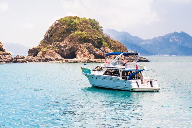 Entspannendes Schnellboot, das nahe kleinen Inseln verankert Schöne Landschaft, Meerblick am sonnigen Tag des Sommers Perfekte Fl stockfotografie