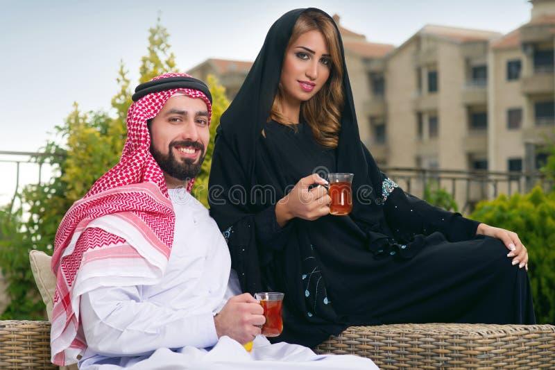 Entspannenu. trinkender Tee der arabischen Paare stockbilder