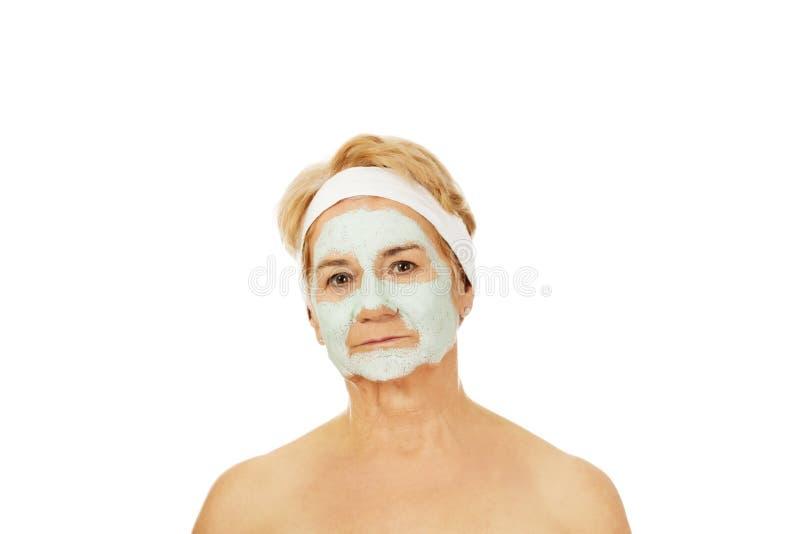 Entspannte ältere Frau in der Gesichtsmaske stockbilder