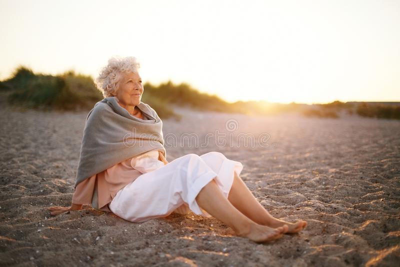 Entspannte ältere Frau, die auf dem Strand sitzt stockbild