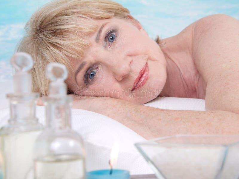Entspannte ältere Frau im Badekurort stockfotos
