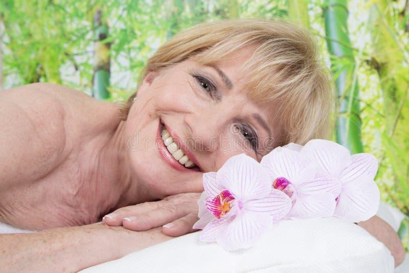 Entspannte ältere Frau im Badekurort lizenzfreies stockfoto