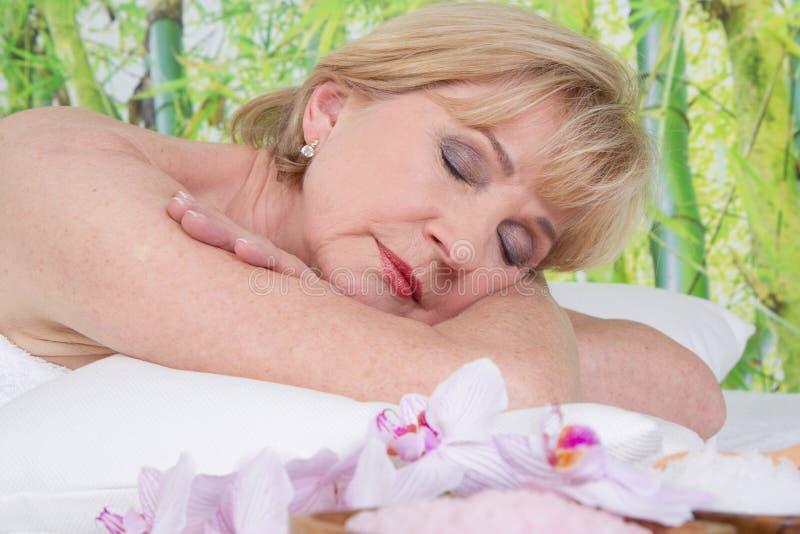 Entspannte ältere Frau im Badekurort mit geschlossenen Augen stockfotografie