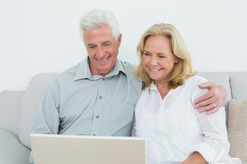 Entspannte ältere Paare unter Verwendung des Laptops zu Hause stockfotografie