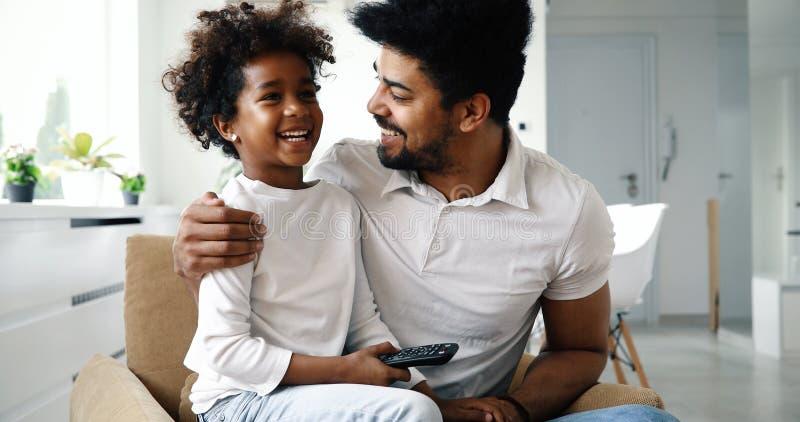 Entspannte Afroamerikanerfamilie, die zu Hause fernsieht lizenzfreies stockbild