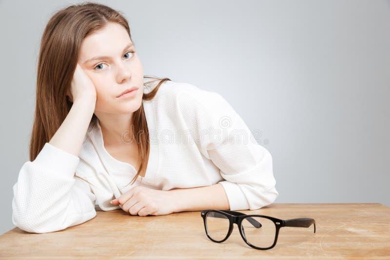 Entspannte attraktive Jugendliche mit den Gläsern, die am Tisch sitzen lizenzfreies stockbild