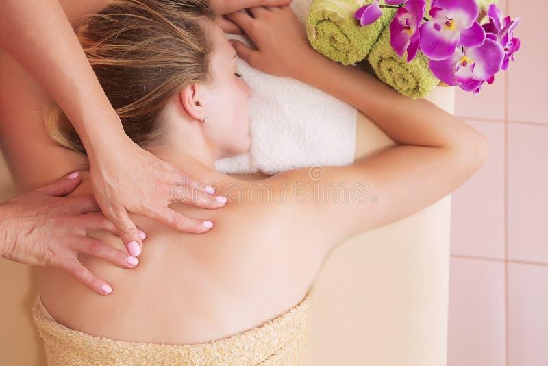 Entspannte Frau auf der Massagetabelle, die Schönheitsbehandlung am Tagesbadekurort empfängt stockfotografie