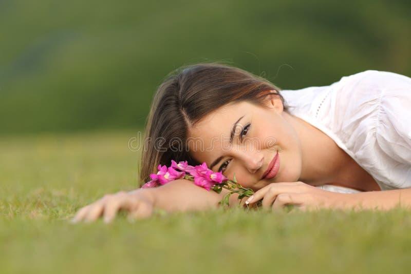 Entspannte Frau, die auf dem grünen Gras mit Blumen stillsteht stockfoto