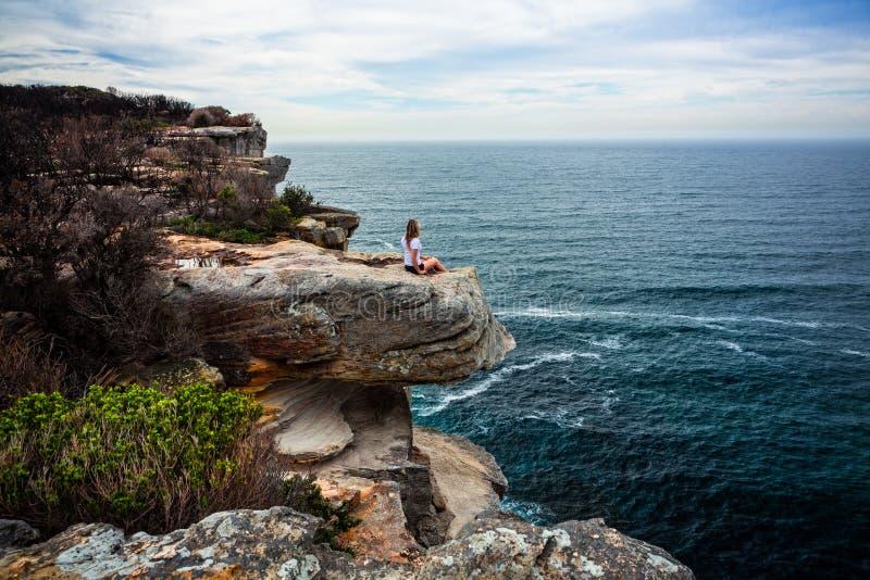 Entspannte Frau, die auf der Küstenlandspitze heraus schaut zum Ozean sitzt lizenzfreies stockbild