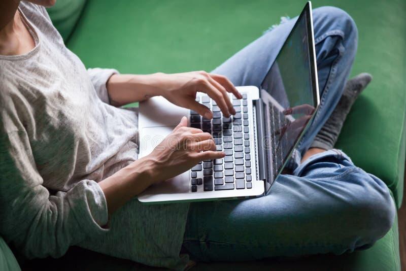 Entspannte Frau, die auf Sofa sitzt und Laptop verwendet lizenzfreie stockbilder
