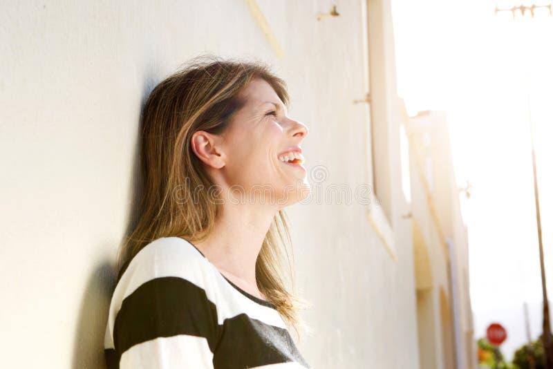 Entspannte Frau, die an der Wand und am Lachen sich lehnt lizenzfreies stockbild