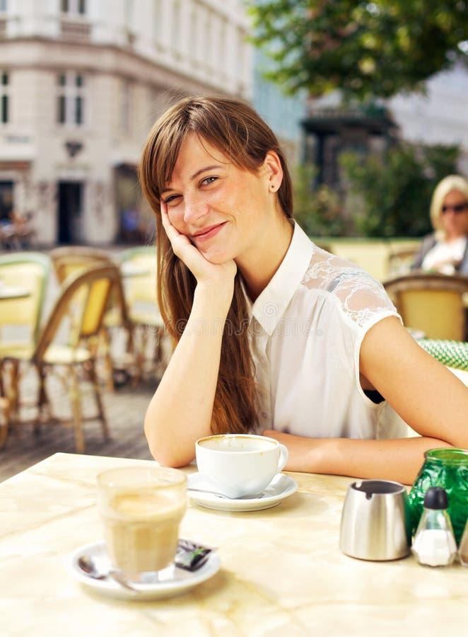 Entspannte Frau, die in einem Freilicht-Café genießt lizenzfreie stockbilder