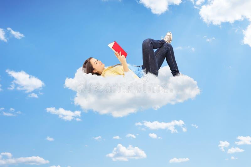 Entspannte Frau, die einen Roman liest und auf Wolken liegt lizenzfreie stockfotos