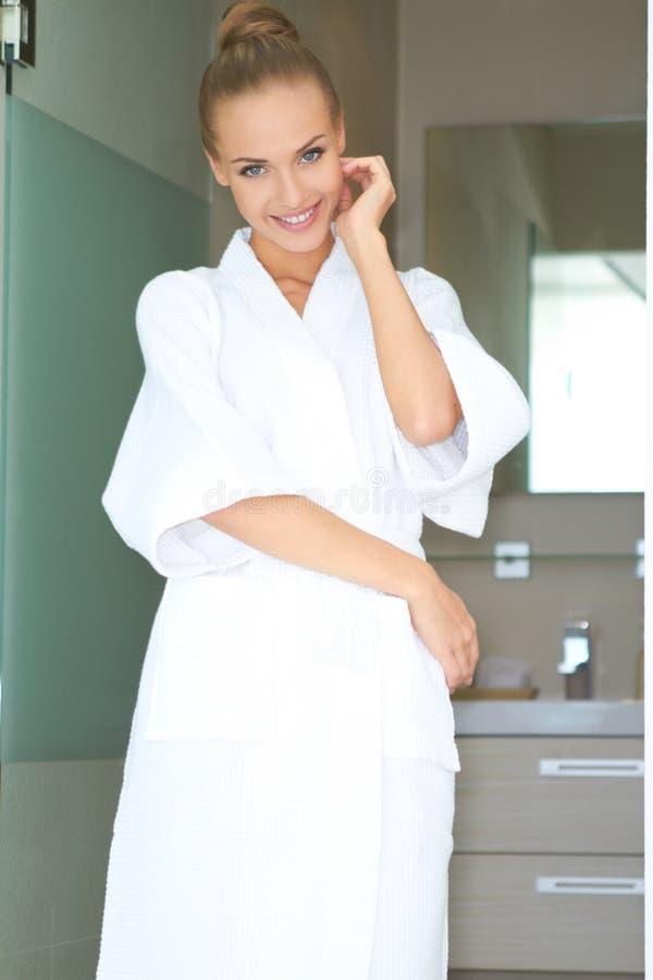 Entspannte Frau, die im weißen Bademantel steht stockfoto