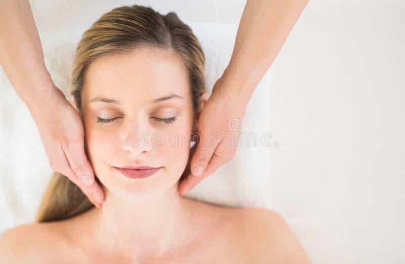 Entspannte Frau, die Kopfmassage im Gesundheits-Badekurort empfängt stockbild