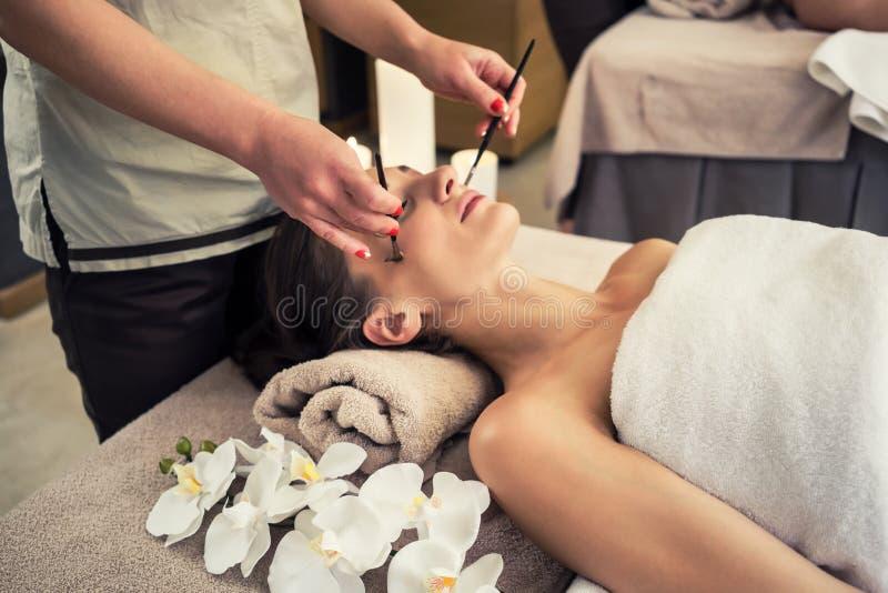 Entspannte Frau, die sich auf Massagebett während der Gesichtsbehandlung hinlegt stockfotografie