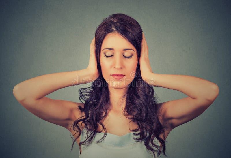Entspannte Frau mit Augen schloss die Abdeckung ihrer Ohren stockfotos