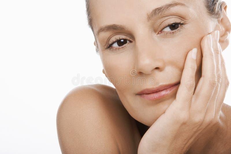 Entspannte Frau mit der Hand auf Chin lizenzfreie stockbilder