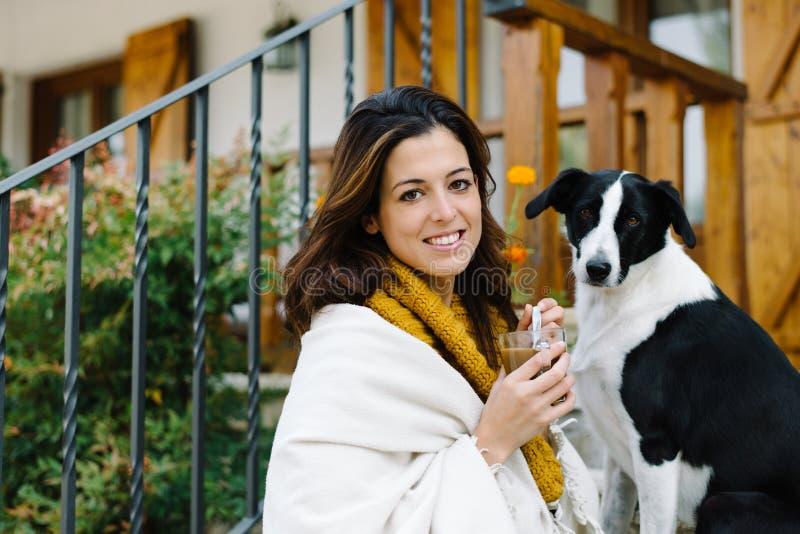 Entspannte Frau mit Hundefreund außerhalb des Hauses auf Herbst stockfotografie