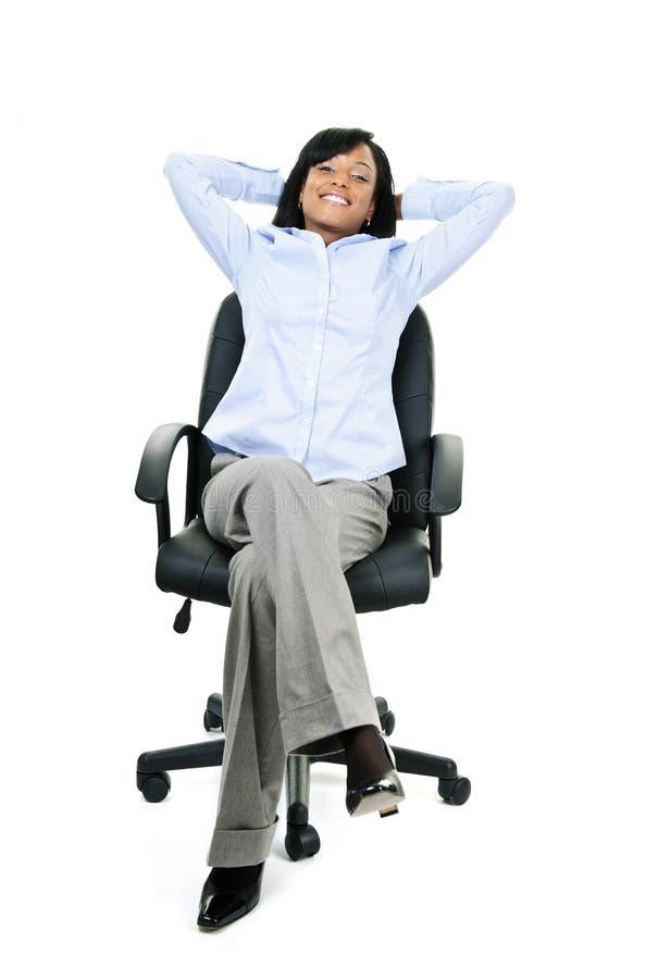 Entspannte Geschäftsfrau, die auf Bürostuhl sitzt lizenzfreies stockbild