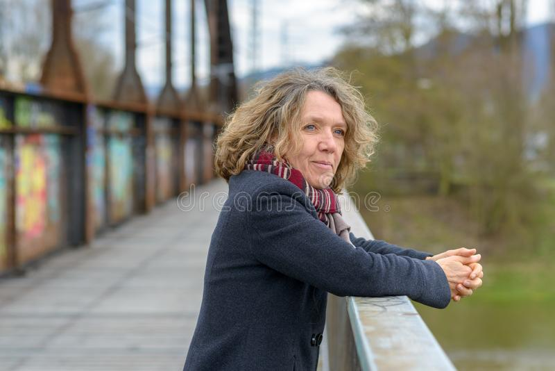 Entspannte glückliche Frau, die auf einem Brückengeländer sich lehnt lizenzfreies stockbild