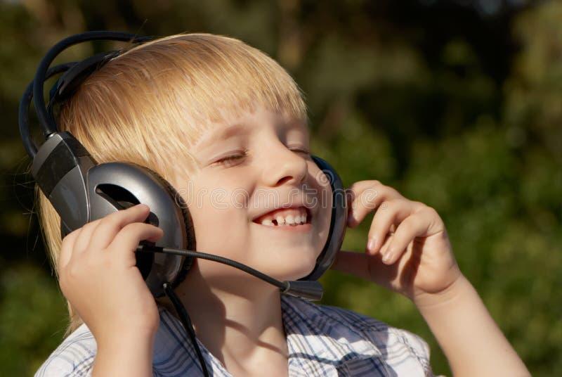 Entspannte hörende Musik des kleinen Jungen stockfotografie