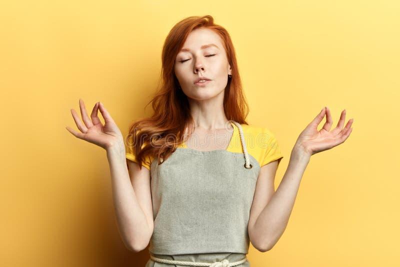 Entspannte Haushälterin, Hausfrau im grauen Schutzblechhändchenhalten in der Yogageste lizenzfreies stockfoto