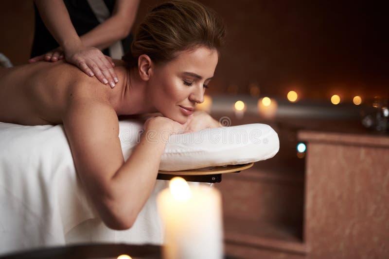 Entspannte junge Dame, die Massage im Badekurortsalon hat lizenzfreies stockbild