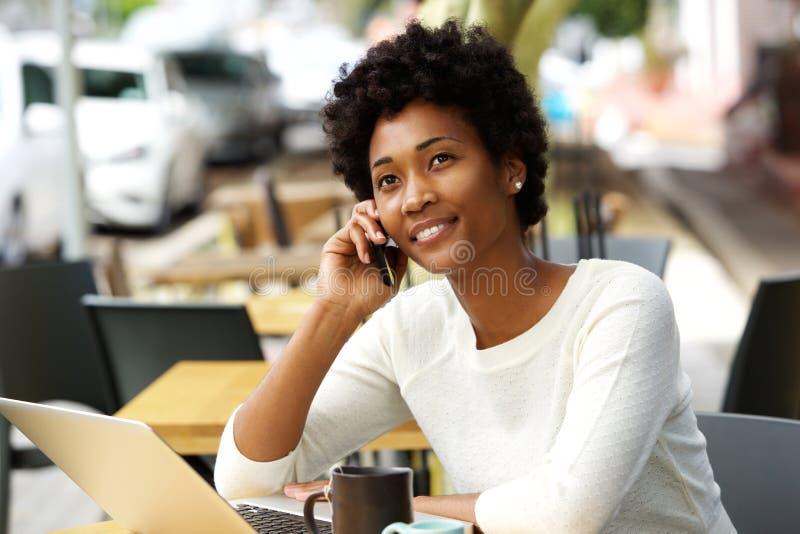 Entspannte junge Frau am Café sprechend am Handy stockfoto