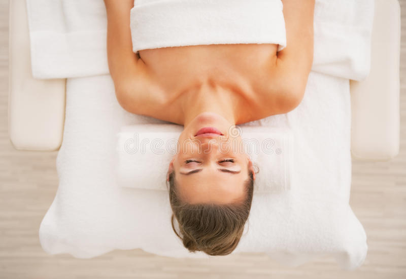 Entspannte junge Frau, die auf Massagetabelle legt lizenzfreie stockfotografie