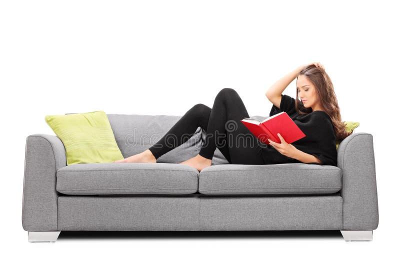 Entspannte junge Frau, die ein Buch gesetzt auf Sofa liest stockbilder