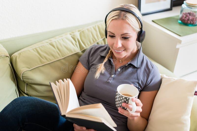 Entspannte junge Frau, die ein Buch liest und Musik hört stockfoto