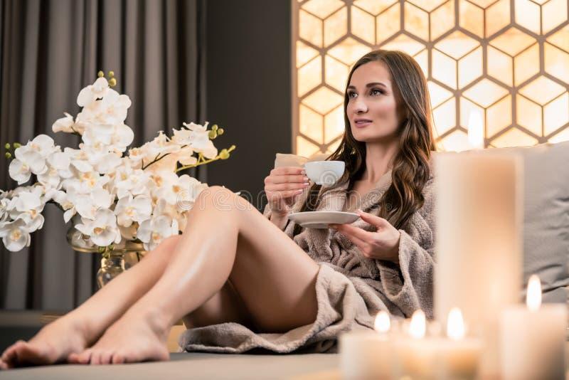 Entspannte junge Frau, die Kräutertee vor Badekur trinkt lizenzfreie stockfotos