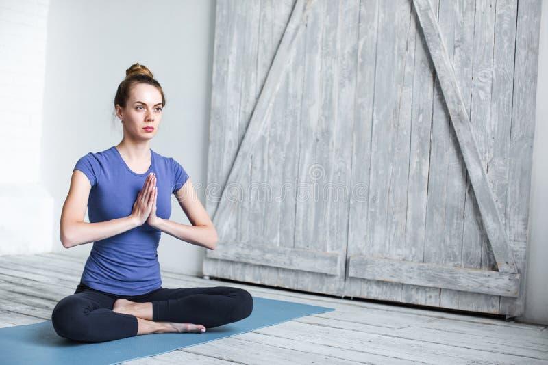 Entspannte junge Frau, die in Lotussitz auf blauer Übungsmatte sitzt lizenzfreie stockfotos