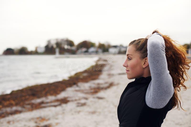 Entspannte junge Frau, die Meer betrachtet stockbild