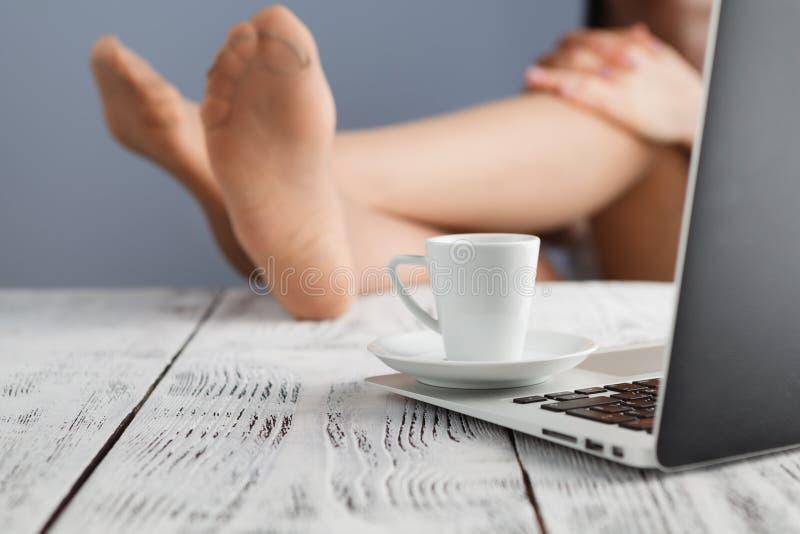 Entspannte junge Geschäftsfrau, die mit den Beinen auf Schreibtisch in einem brigh sitzt stockbilder