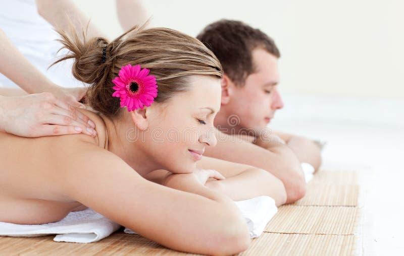 Entspannte junge Paare, die eine rückseitige Massage empfangen stockfotos