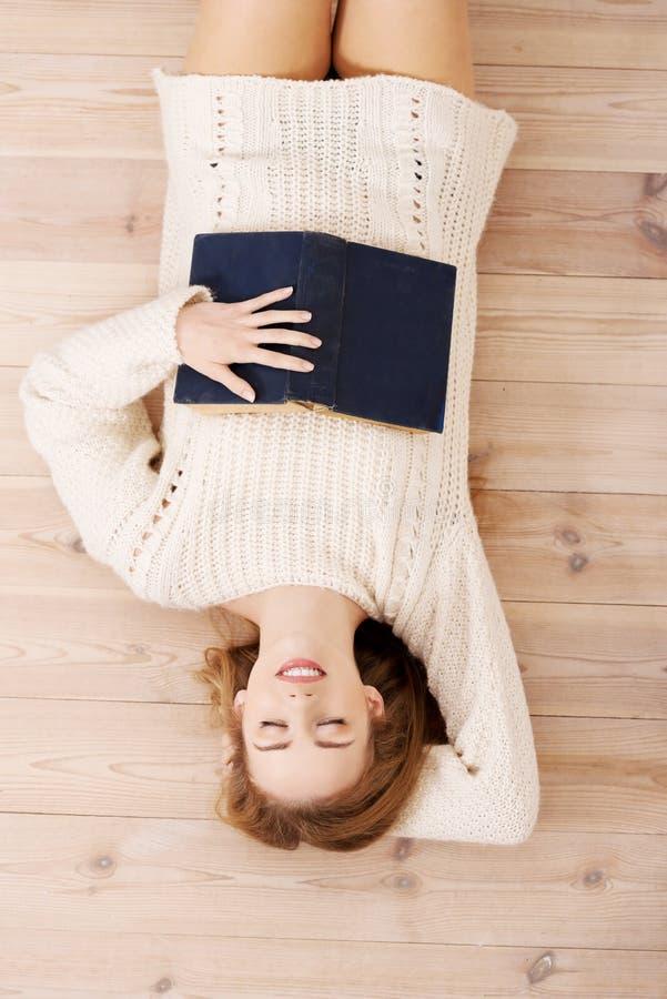 Entspannte junge Studentenfrau, die auf dem Boden liegt stockbilder