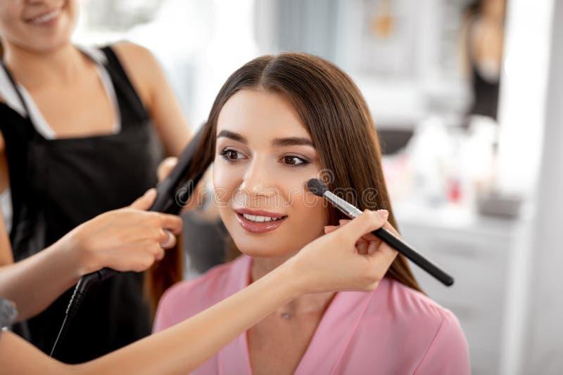 Entspannte lächelnde und Kosmetikerhandeln Dame machen sie wieder gut lizenzfreie stockfotografie