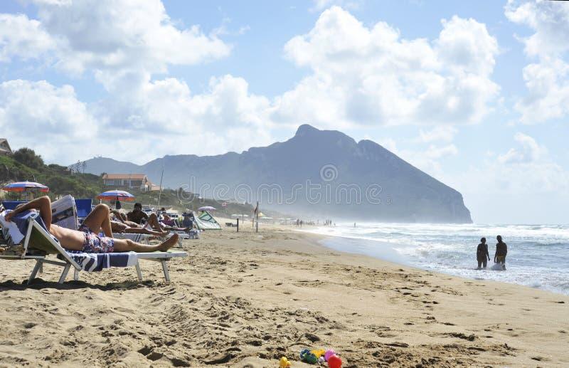 Entspannte Leute auf dem Sabaudia setzen f?r die Sommerferien auf den Strand Der Circeo-Berg auf dem Hintergrund Sabaudia, Lazio, stockfotos