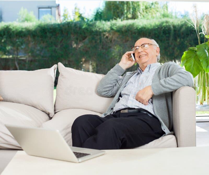 Entspannter älterer Mann, der Mobiltelefon auf Couch verwendet lizenzfreie stockfotos