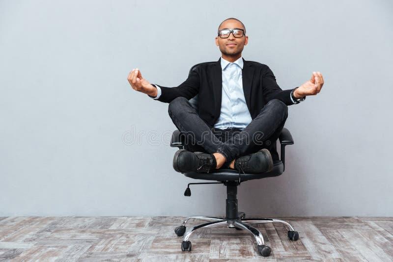 Entspannter afrikanischer junger Mann, der auf Bürostuhl sitzt und meditiert stockfotografie