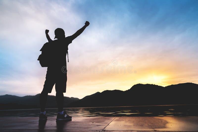 Entspannter asiatischer Mannreisender mit dem Rucksack, der zum Sonnenuntergang schaut stockbild