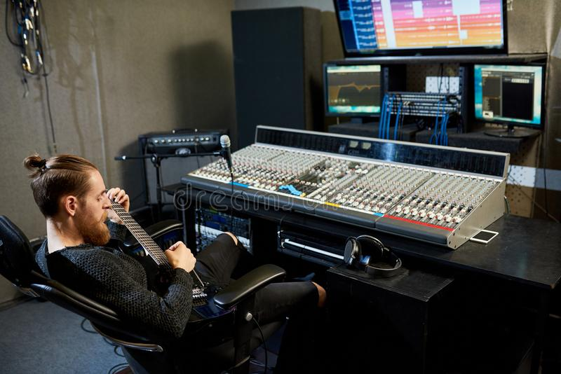 Entspannter Audioingenieur, der Pause macht, um Gitarre zu spielen stockfoto