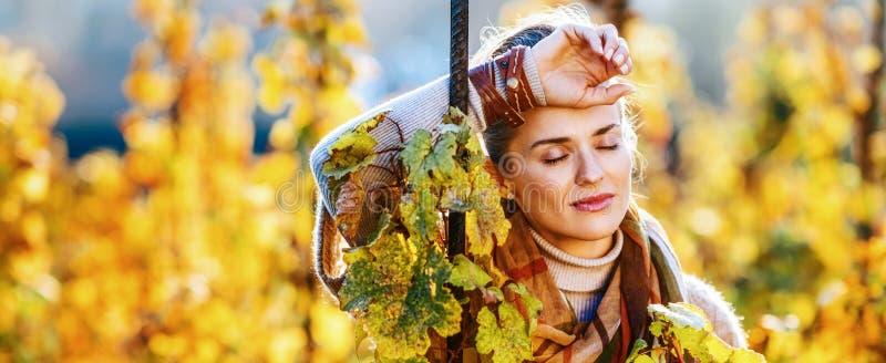 Entspannter Frauenweinbauer, der draußen im Weinberg im Herbst steht stockbild