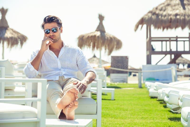Entspannter gutaussehender Mann, der auf weißen Stühlen während des Sommers sitzt lizenzfreies stockbild