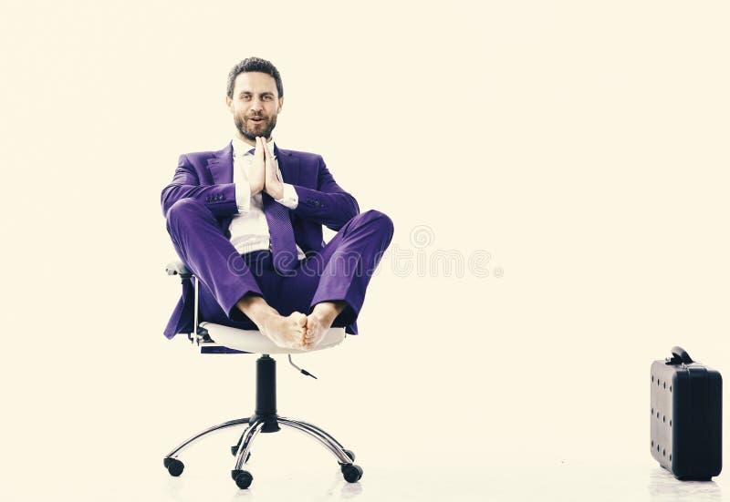 Entspannter hübscher kaukasischer junger Mann, der auf dem Bürostuhl, lokalisiert auf weißem Hintergrund sitzt und meditiert lizenzfreies stockfoto