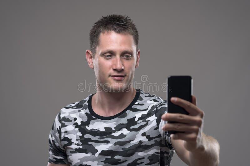 Entspannter junger erwachsener Mannesholdinghandy und nehmen Fotos oder selfie lizenzfreies stockfoto